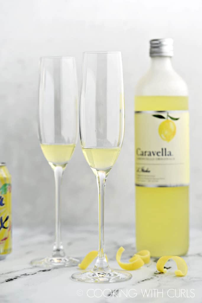 Limoncello in two champagne flutes with the bottle in the background and lemon rinds laying on the marble top.
