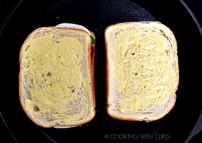 Looking down on two butter topped slices of bread in a cast iron skillet.