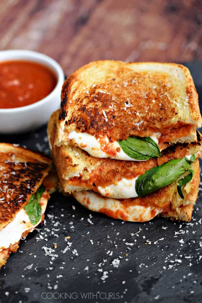 Two pizza Margherita grilled cheese sandwiches cut in half and stacked on top of each other on a black slate platter with a small bowl of pizza sauce in the background.