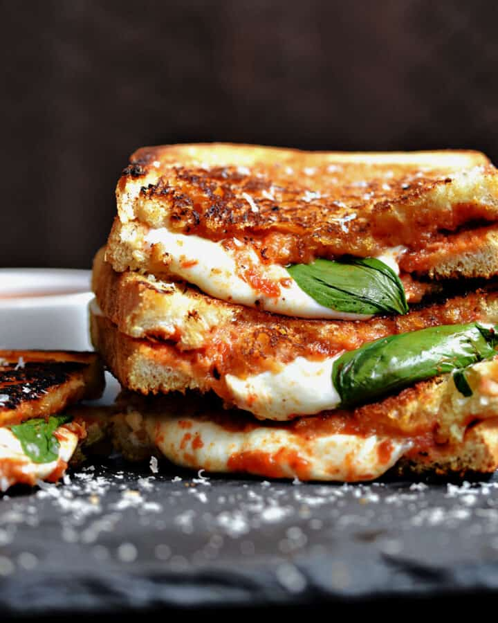 A close up image of one and a half Pizza Margherita Grilled Cheese sandwiches stacked on top of each other with a fourth sitting next to the stack.