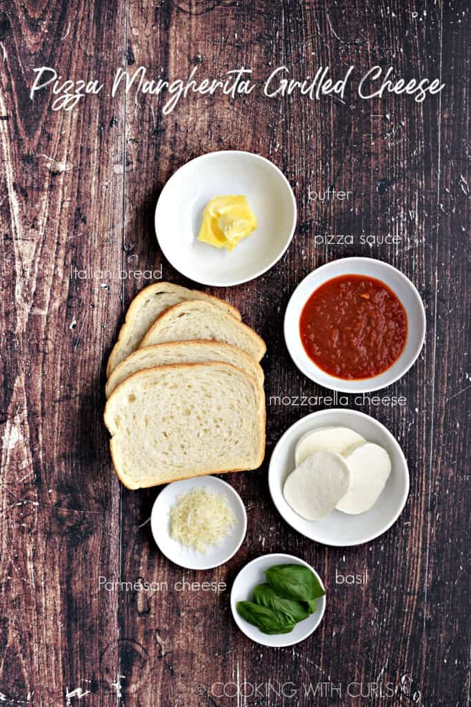 Pizza Margherita Grilled Cheese ingredients_ sliced bread, butter, pizza sauce, mozzarella cheese, fresh basil leaves, Parmesan cheese in white bowls.