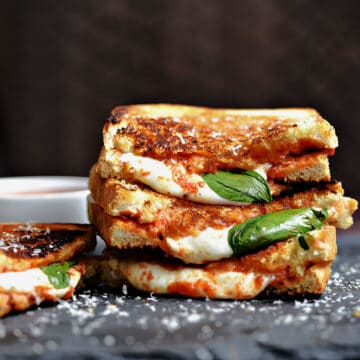 one and a half Pizza Margherita Grilled Cheese sandwiches stacked on top of each other with a fourth sitting next to the stack.