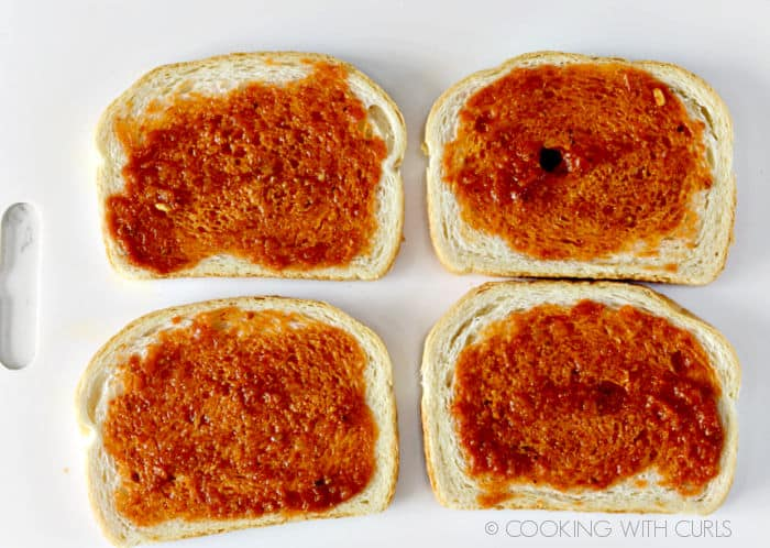 Pizza sauce spread over four slices of white bread.