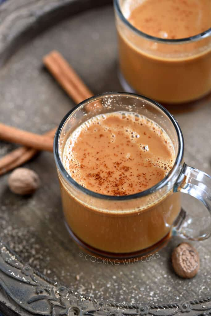 Two clear glass mugs filled with hot buttered rum and topped with grated nutmeg.