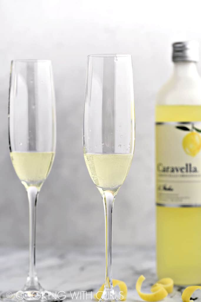 Sparkling lemon water added to the limoncello in the two flutes with a bottle of limoncello in the background.