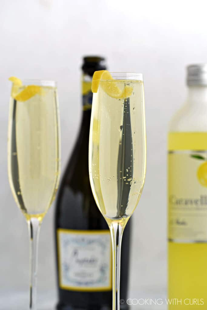Two champagne flutes with limoncello, prosecco and lemon sparkling water with a lemon twist.