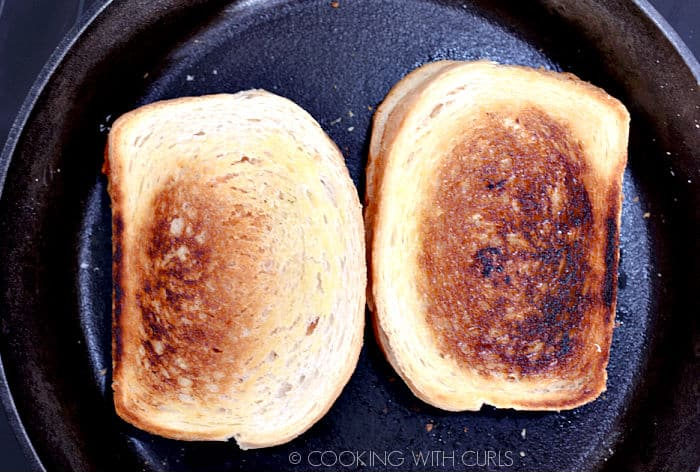 Two grilled cheese sandwiches in a cast iron skillet.