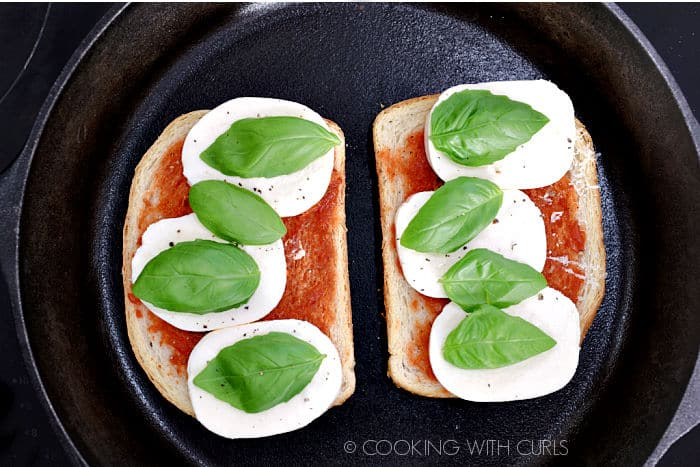 Two slices of bread topped with sauce, mozzarella cheese and basil leaves butter side down in a cast iron skillet.