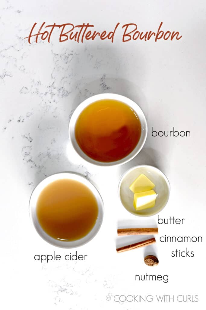 White bowls with bourbon, apple cider, butter and two cinnamon sticks and piece of nutmeg laying on a marble counter and title graphic running across the top.