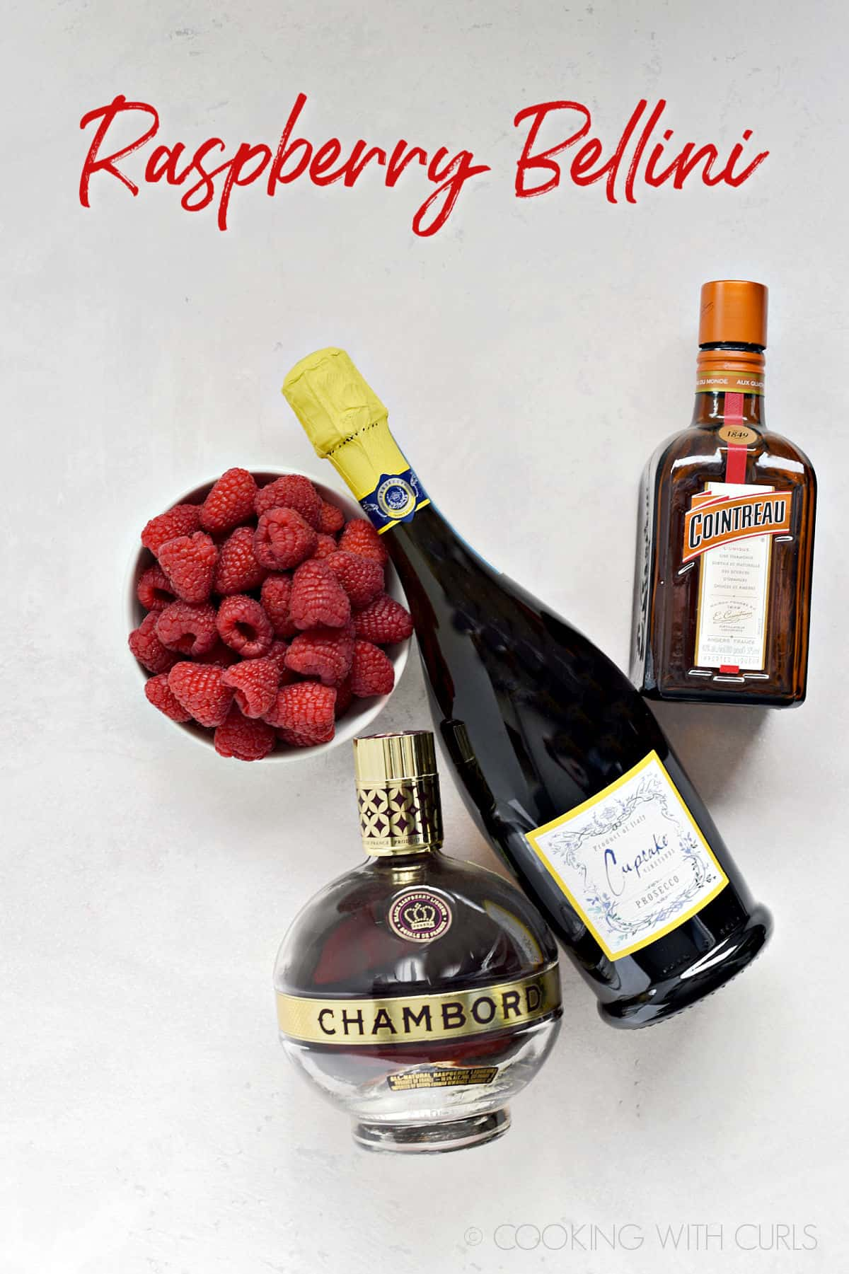 A bowl of fresh raspberries and bottles of prosecco, Cointreau and Chambord.