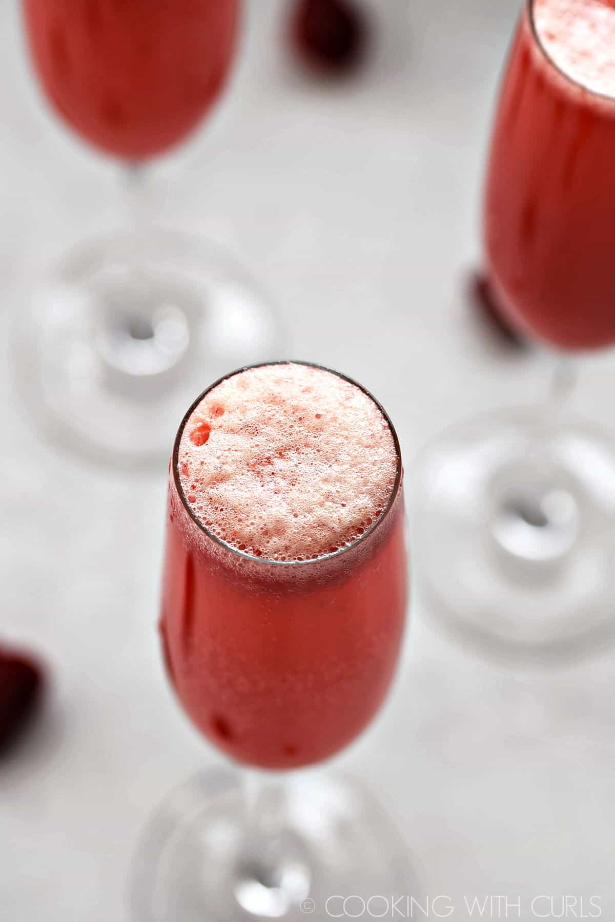 Looking down on a bubbly Raspberry Bellini in a champagne flute with two others in the background.