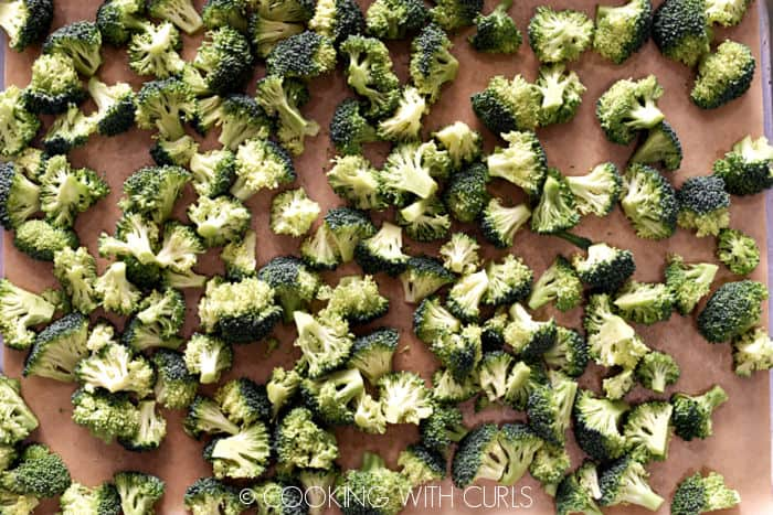 Broccoli florets on a parchment lined baking sheet.