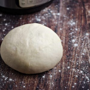 A ball of dough on a wood surface with an Instant Pot in the background.
