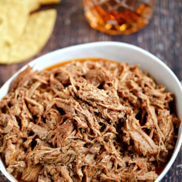 pulled pork in a white bowl with tortilla chips and a glass of whiskey in the background.