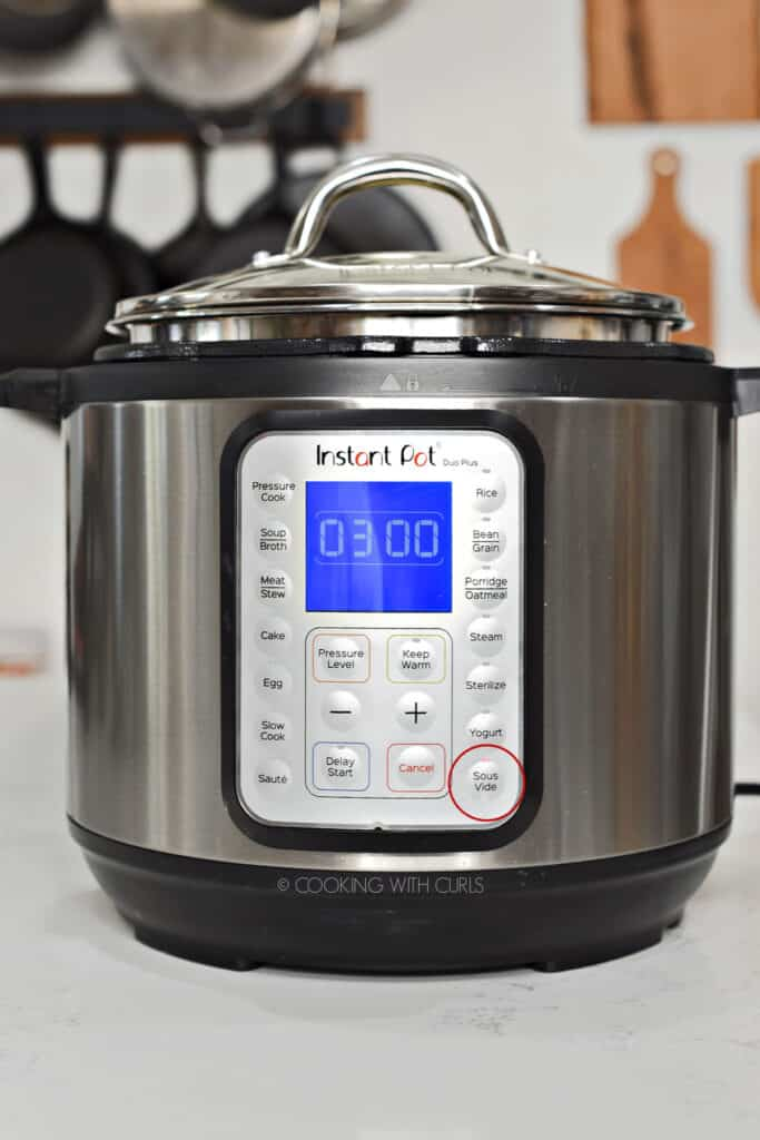 Instant Pot with 03 00 on the display and red circle around the Sous Vide button.