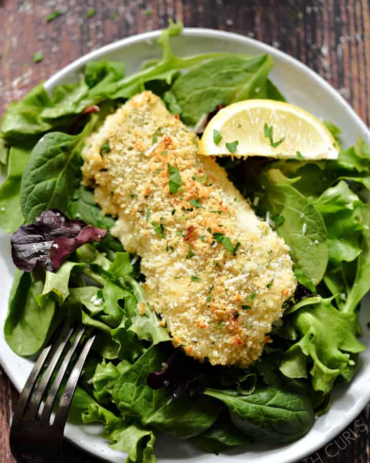 A close-up image looking down on a panko crusted fish filet on a bed of leafy greens with a lemon wedge on the side.