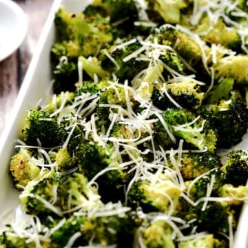 Oven Roasted Broccoli in a white, rectangle platter topped with grated Parmesan.