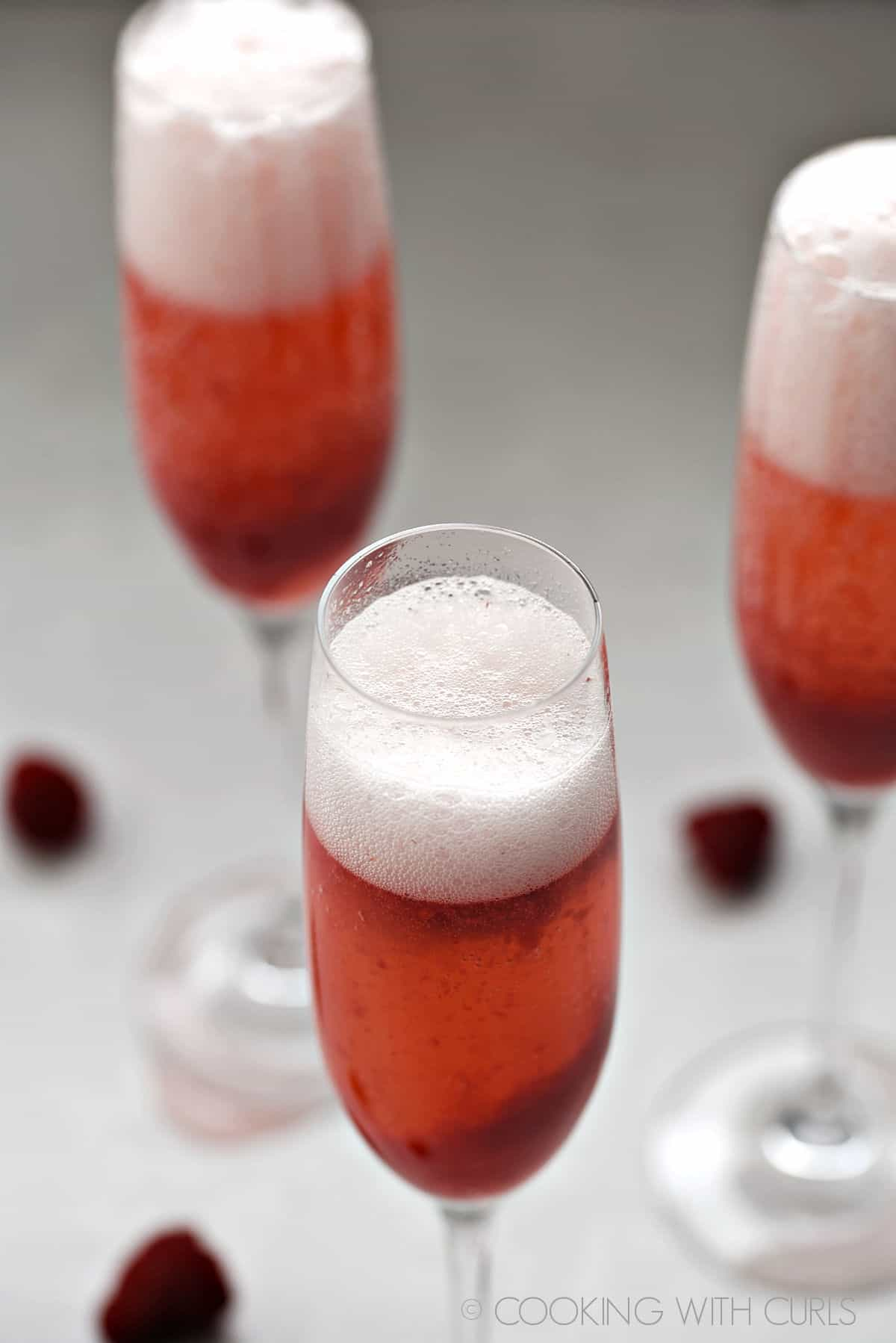 Prosecco added to the raspberry puree in the champagne flutes.