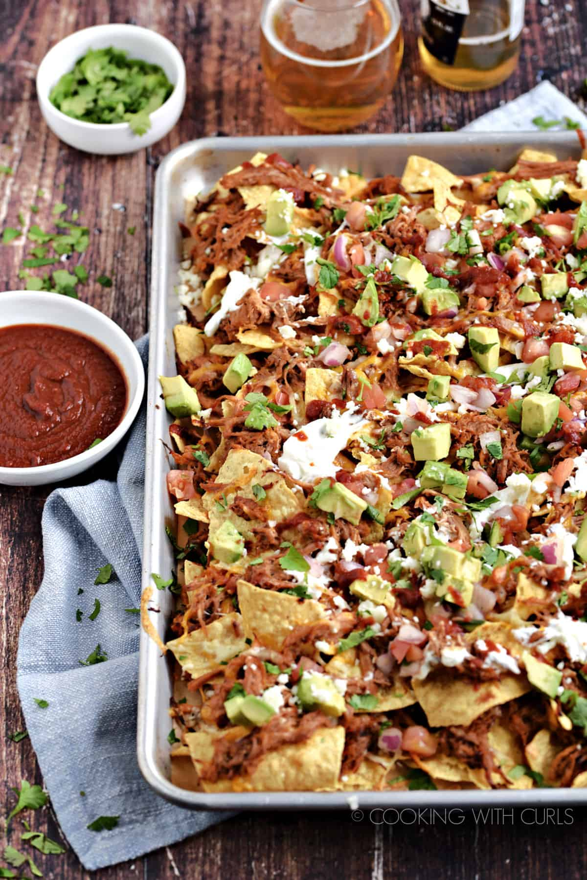 A sheet pan filled with Pulled Pork Nachos topped with avocado, sour cream, salsa and barbecue sauce.