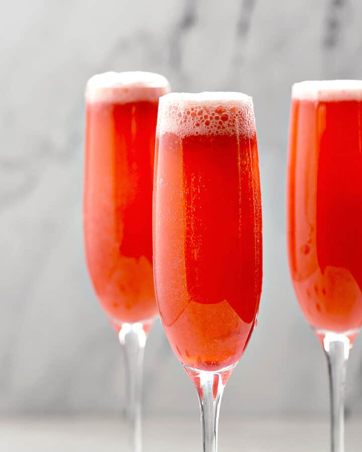 Three Raspberry Bellini Cocktails in champagne flutes.