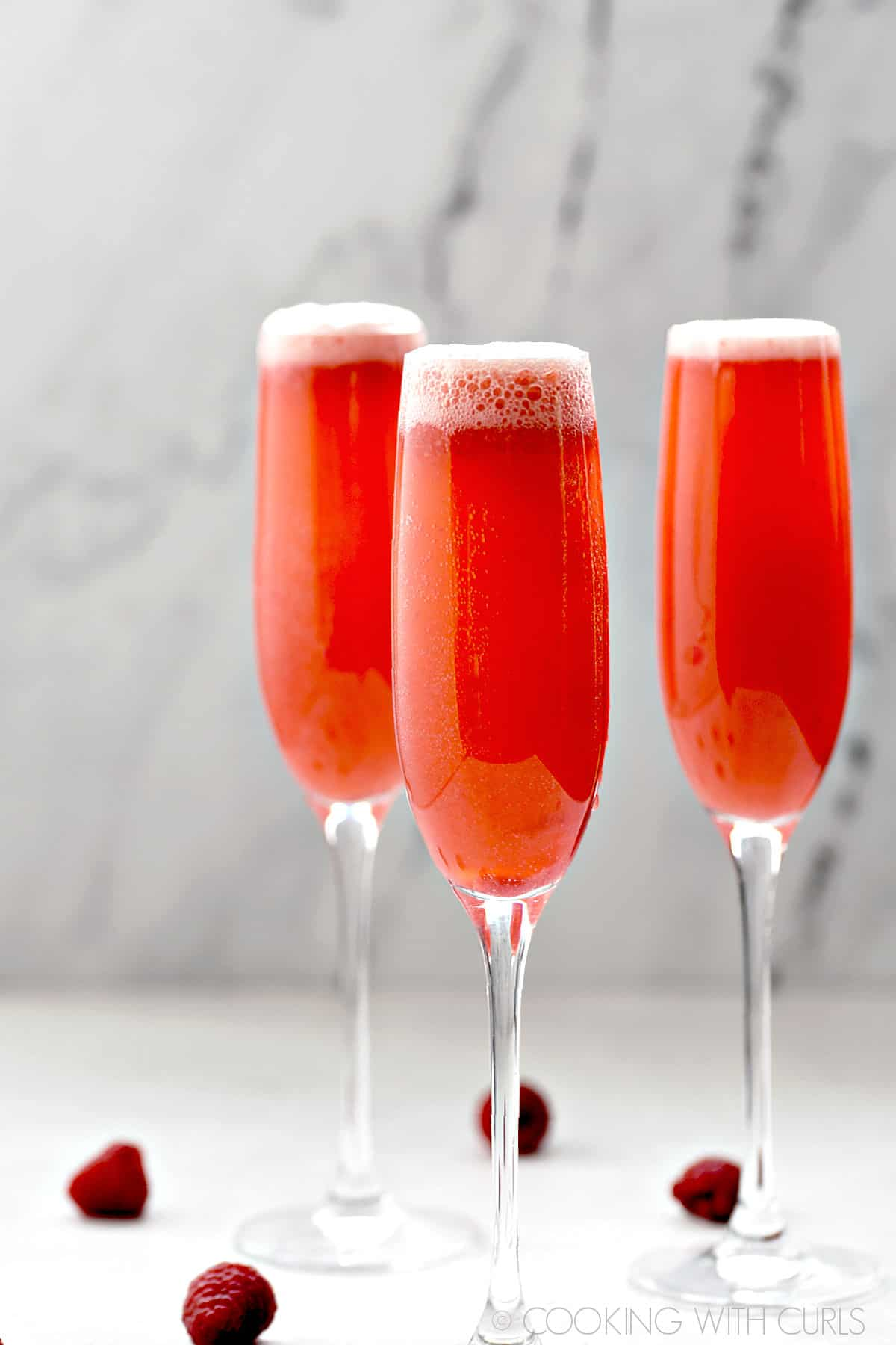 Three champagne flutes filled with Raspberry Bellini.