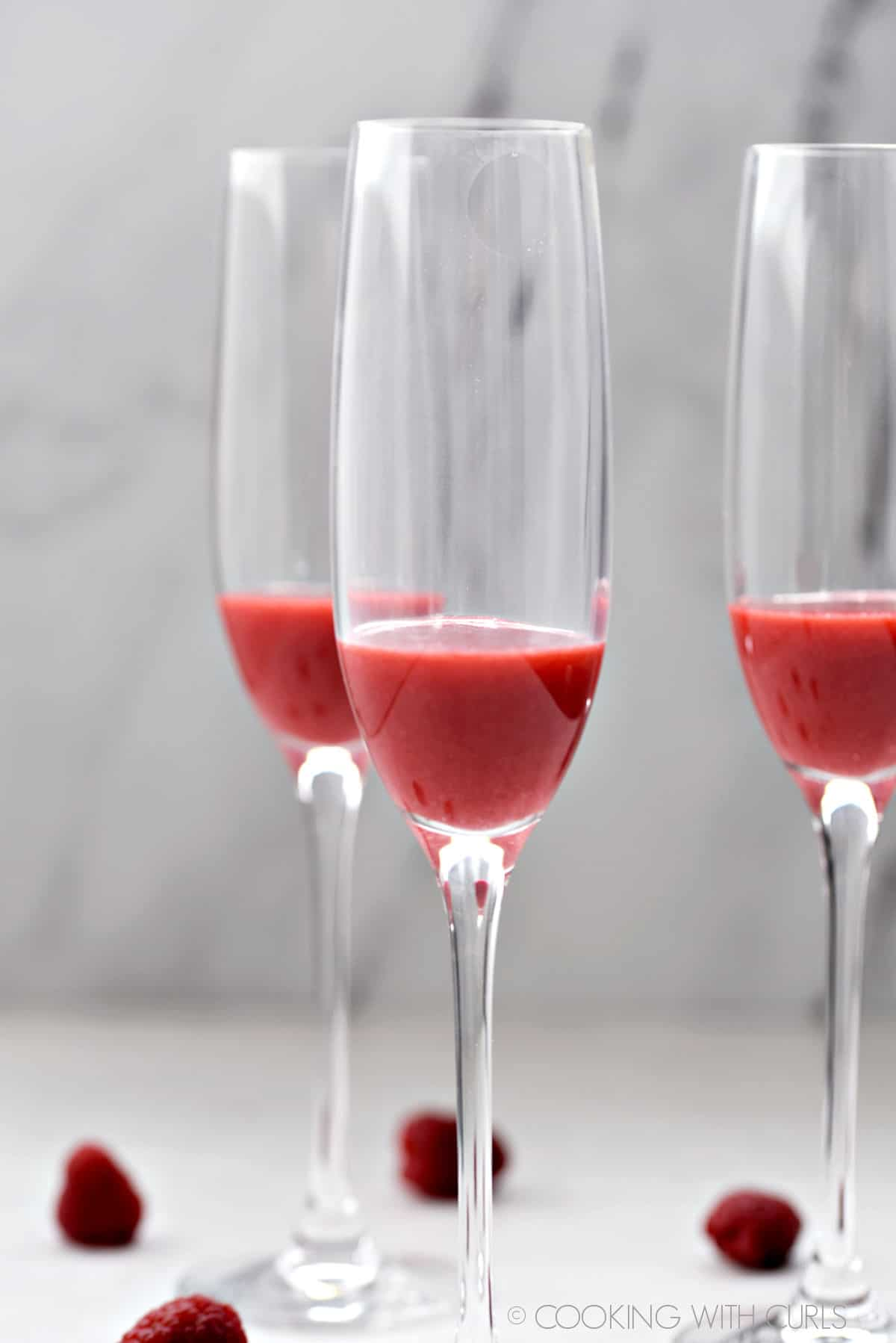 Raspberry puree in the bottom of three champagne flutes.