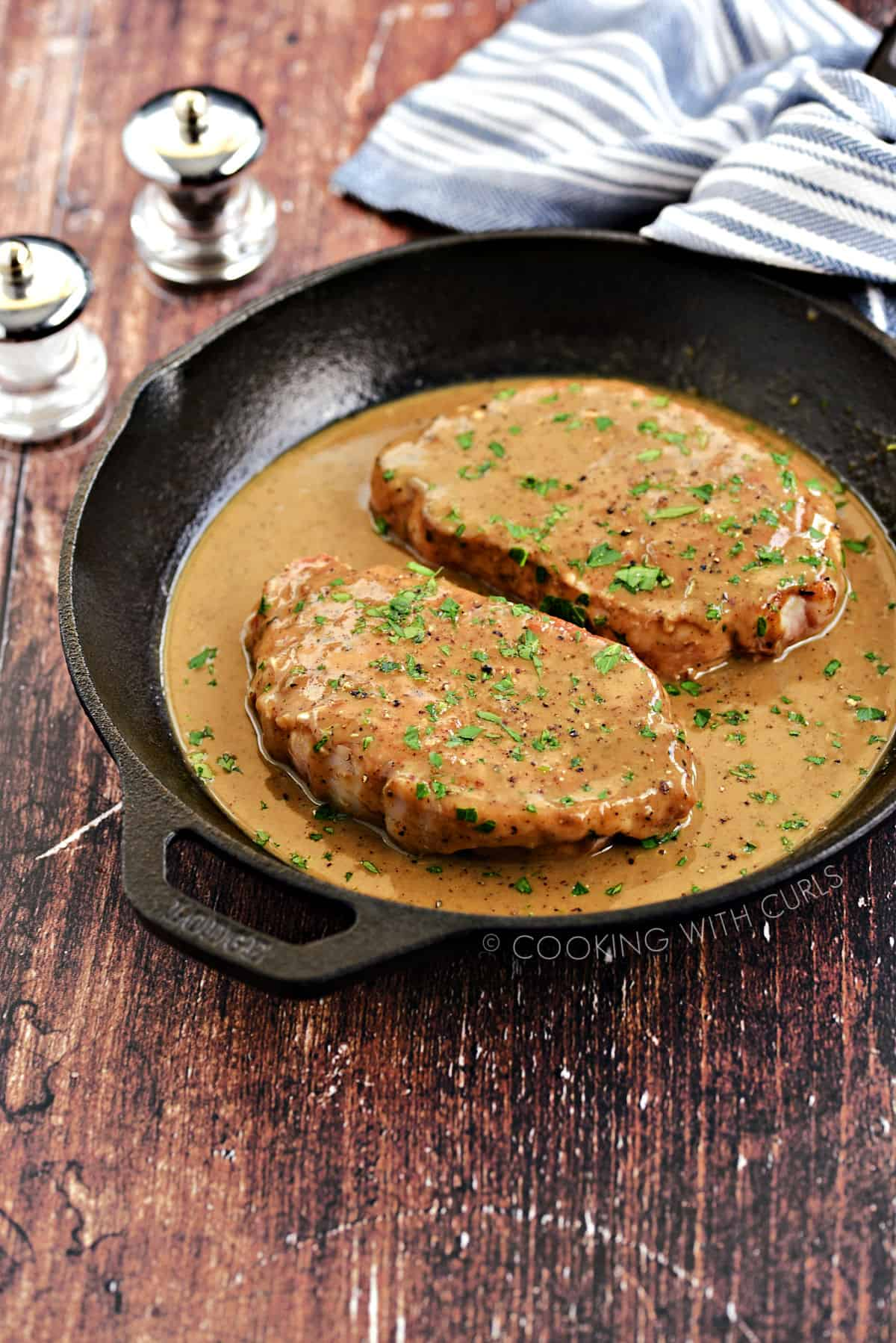 Two pork chops smothered with brown pan gravy in a cast iron skillet.
