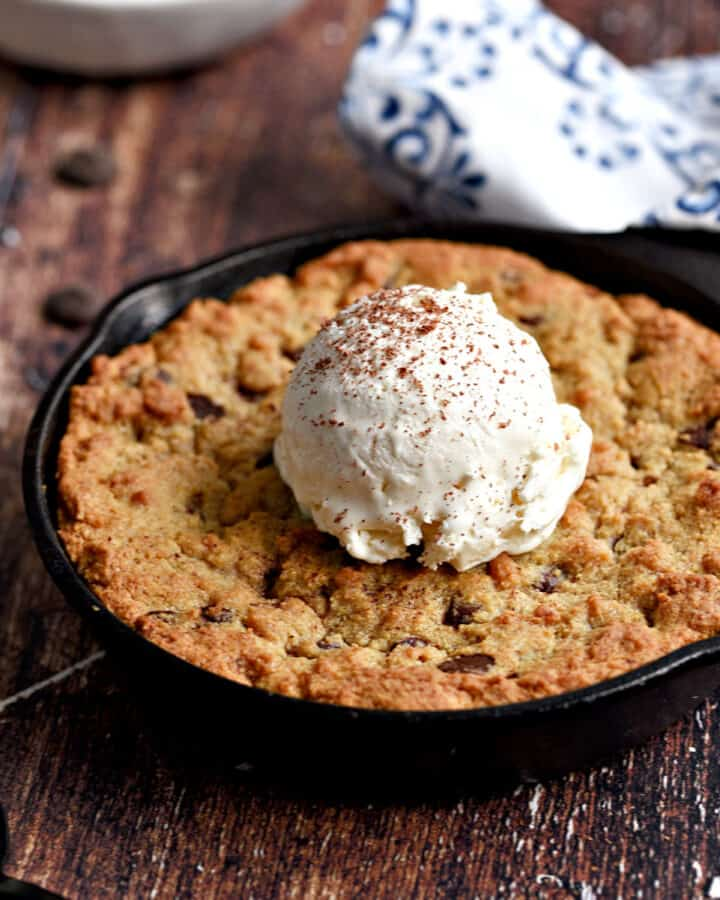 A mini Skillet Chocolate Chip Cookie for Two topped with a scoop of vanilla ice cream.