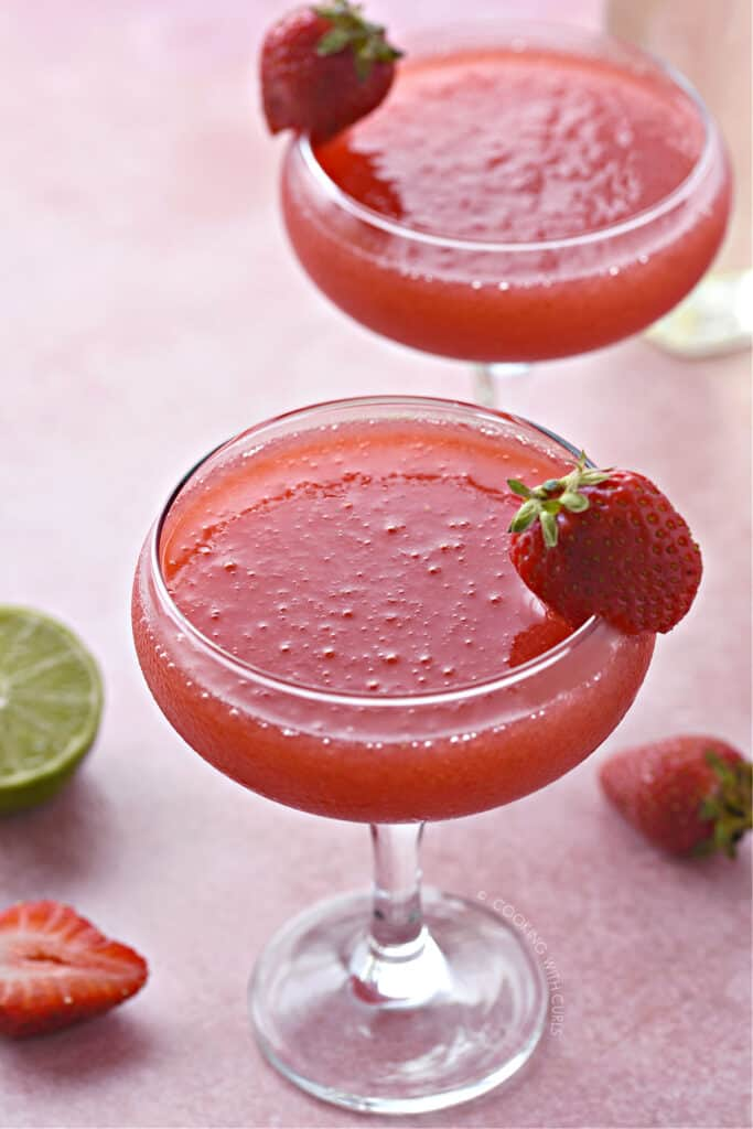 Two coupe glasses filled with frozen strawberry daiquiri with a small strawberry on the rim.