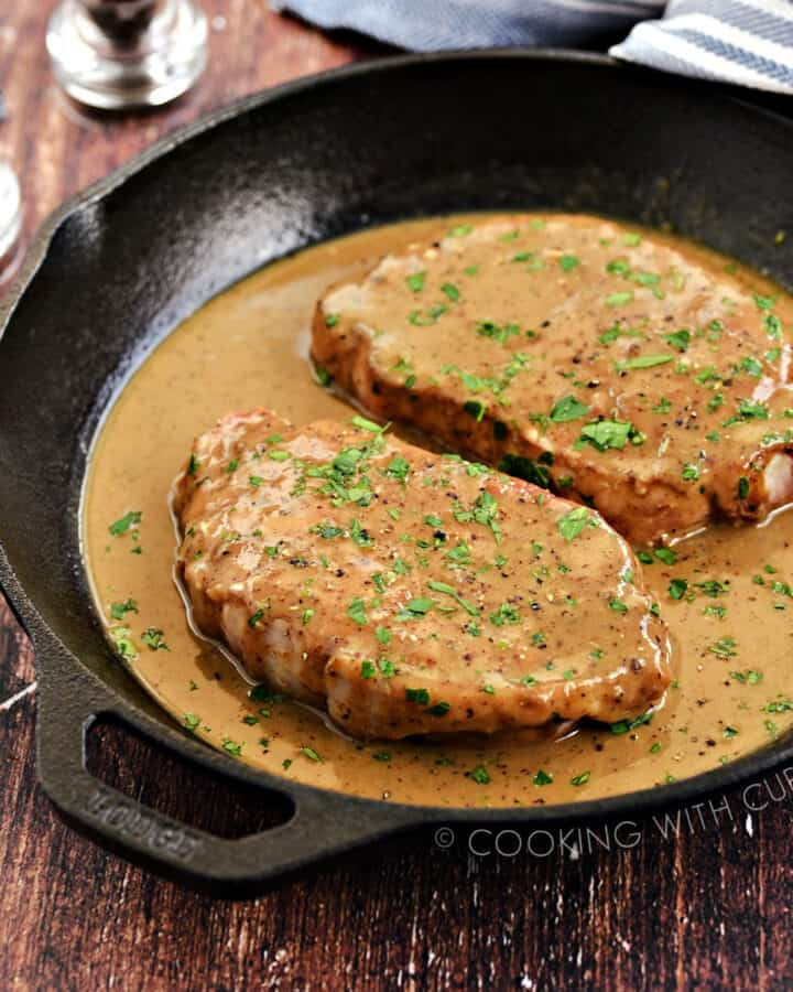 Two Pork Chops with Pan Gravy in a cast iron skillet.