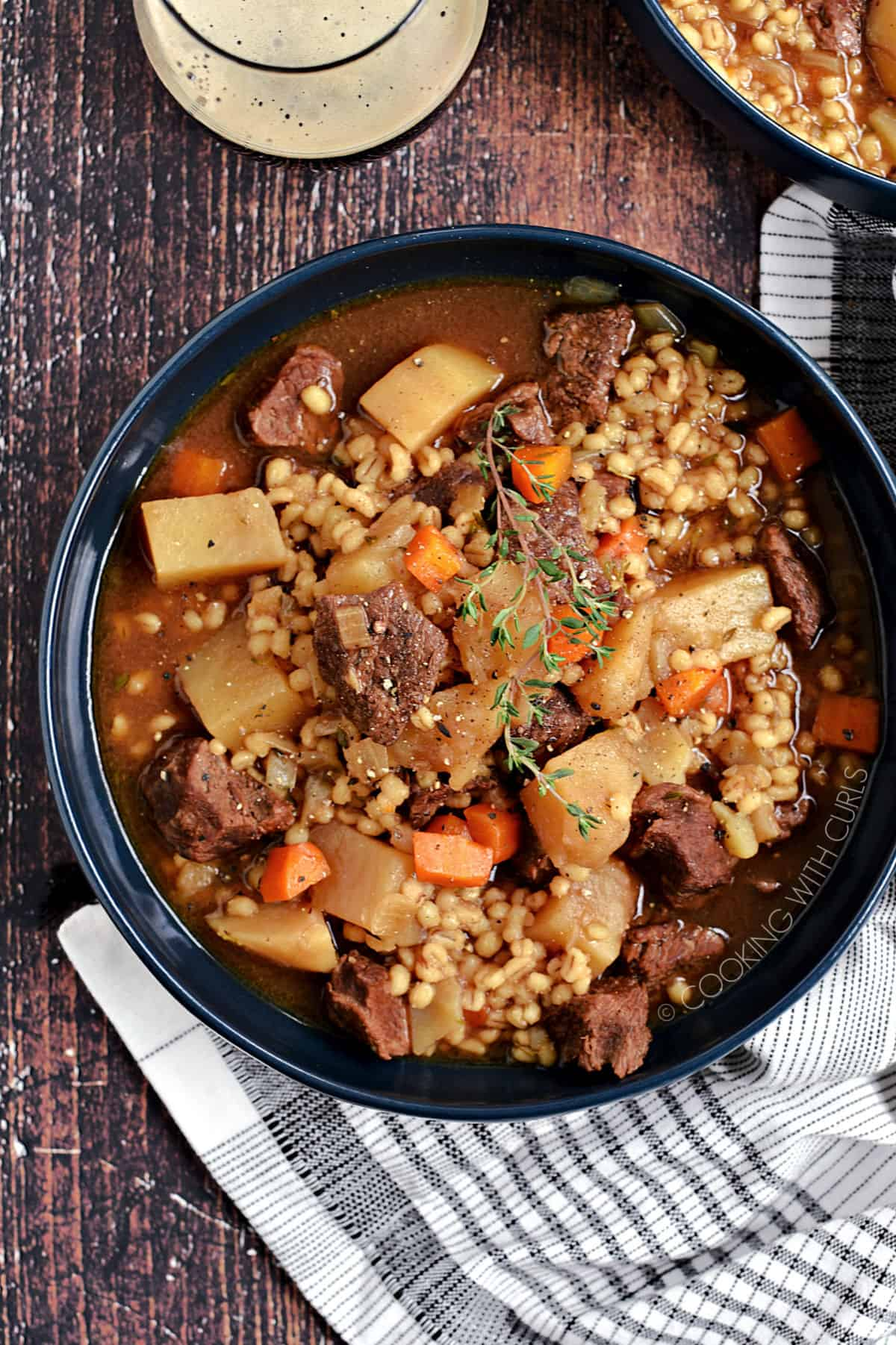 Looking down on a big blue bowl of beef, potato and carrots chunks surrounds by broth and barley.