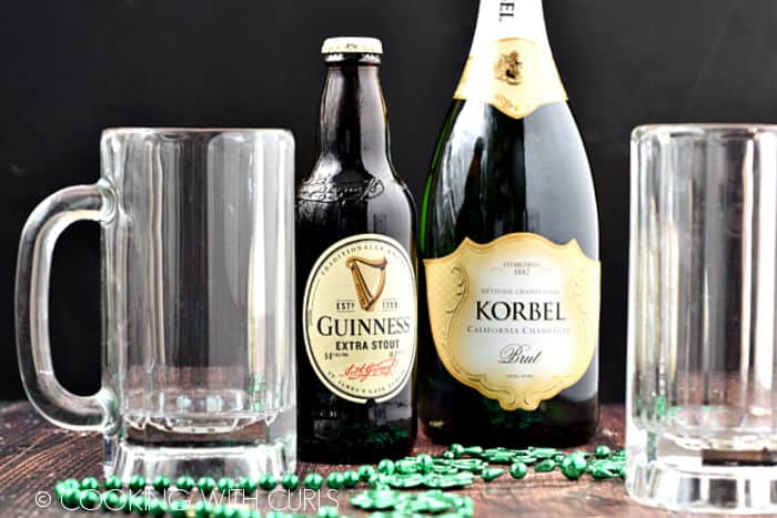 A bottle of Guinness beer, a bottle of Korbel champagne and two empty beer tankards with green beads on a wooden surface.