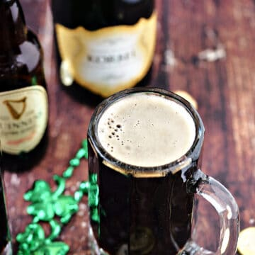 Foamy, black cocktail in a glass beer mug surrounded by green beads with bottles of Guinness and champagne in the background.