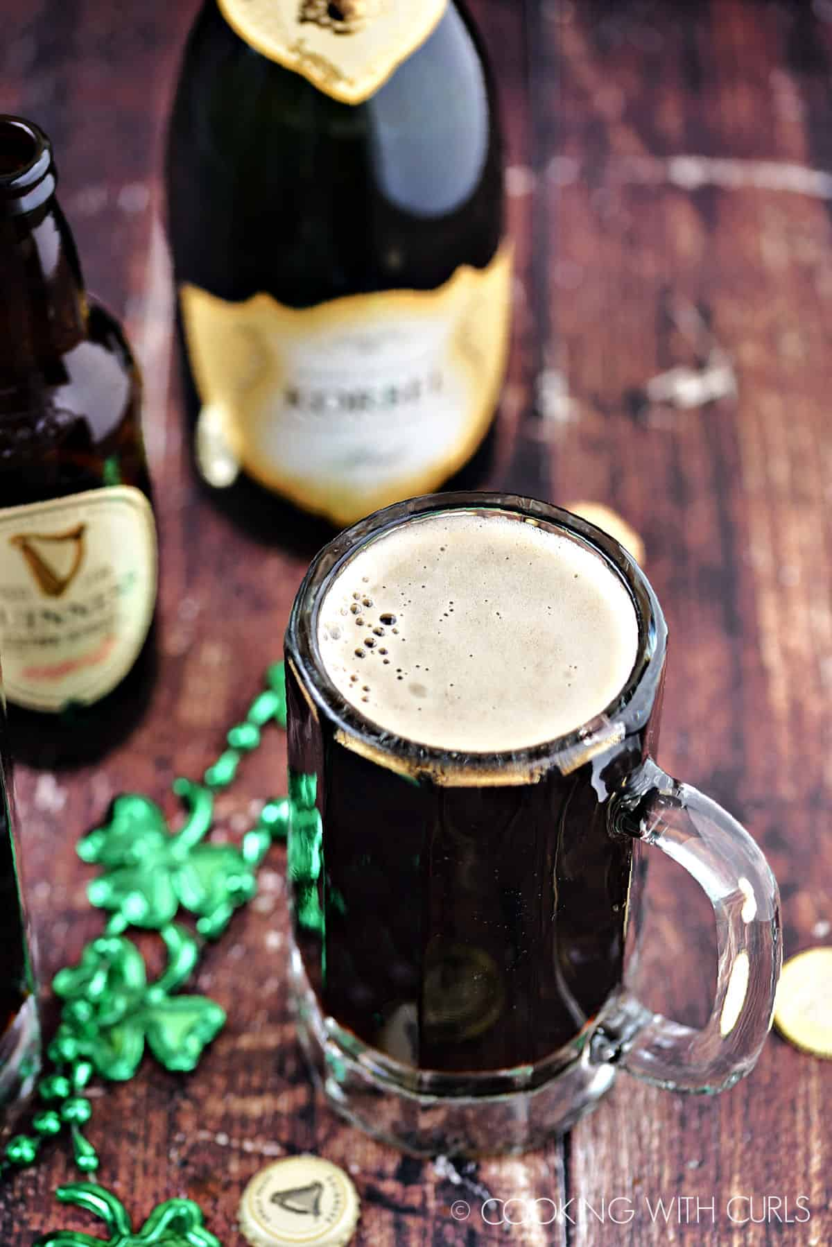 Foamy, black cocktail in a glass beer mug with bottles of Guinness and champagne in the background.