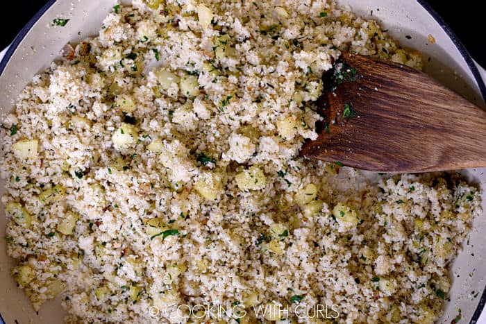 Breadcrumbs stirred into the mixture in the skillet with a wooden turner.