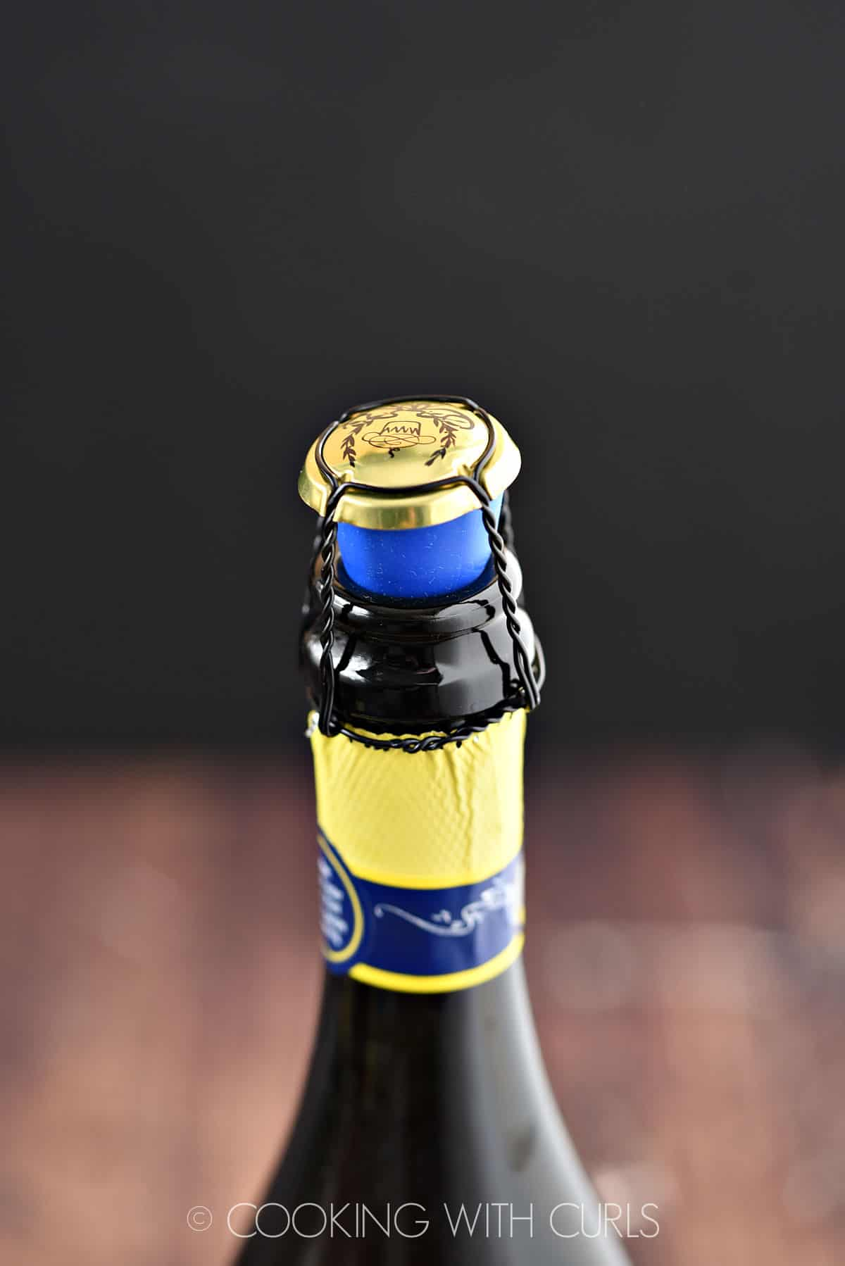 Cage and blue silicone stopper on champagne bottle.