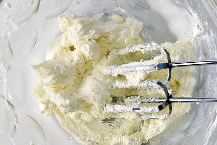 Cream cheese and sugar beaten with a hand mixer in a glass bowl.