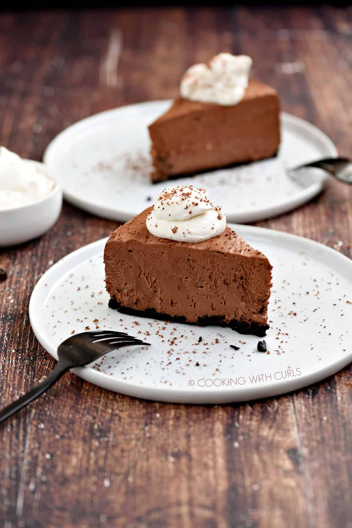 A slice of chocolate cheesecake topped with whipped cream and sprinkled with shaved chocolate sitting on a white plate with a second slice and a bowl of whipped cream in the background.