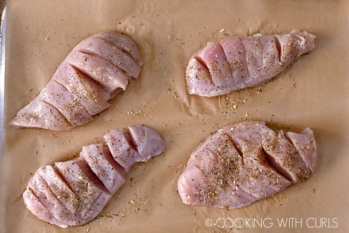 Four chicken breasts on a parchment lined baking sheet covered in seasonings with slits cut into the flesh.