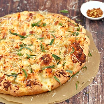 A whole lobster pizza sprinkled with Parmesan and tarragon leaves.