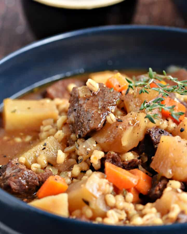 Instant Pot Beef and Barley Stew with potatoes and carrots in a blue bowl.