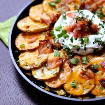 Thinly sliced potatoes arranged in a cast iron skillet topped with melted cheese, bacon, sour cream, salsa and green onions.