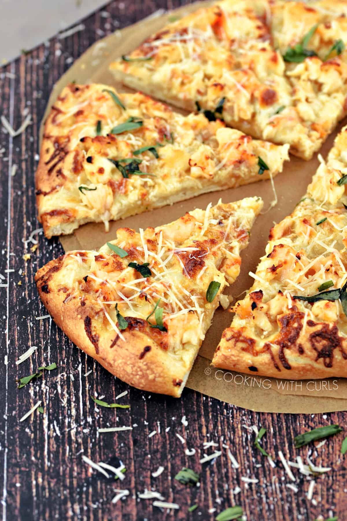 A Lobster Pizza cut into 8 slices sitting on parchment paper circles and sprinkled with tarragon and Parmesan cheese shreds.