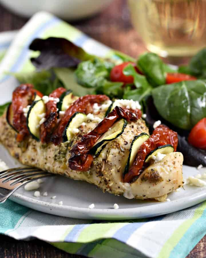 Chicken breast stuffed with pesto, sun-dried tomatoes and zucchini slices on a plate with mixed greens and cherry tomatoes.
