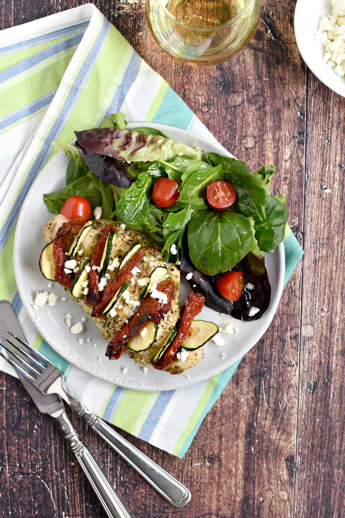 Mediterranean Hasselback Chicken Breast with sun-dried tomatoes, zucchini, pesto and feta cheese served on a plate with mixed greens and cherry tomatoes.