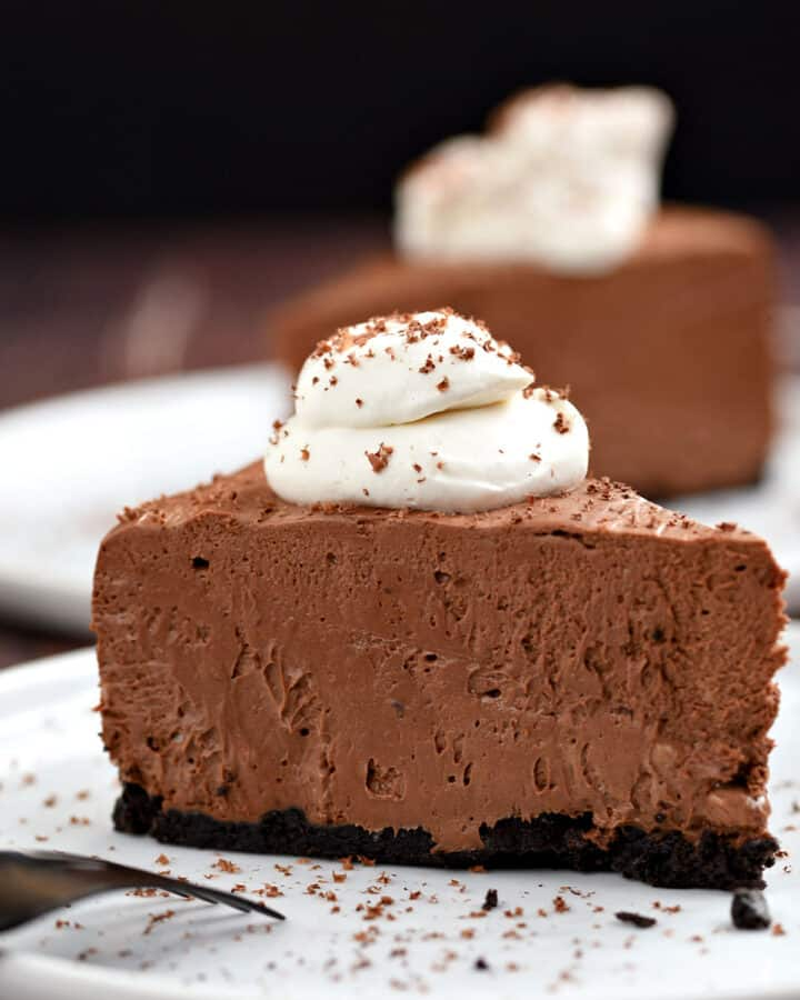 A slice of chocolate cheesecake topped with whipped cream and sprinkled with shaved chocolate sitting on a white plate with a second slice in the background.