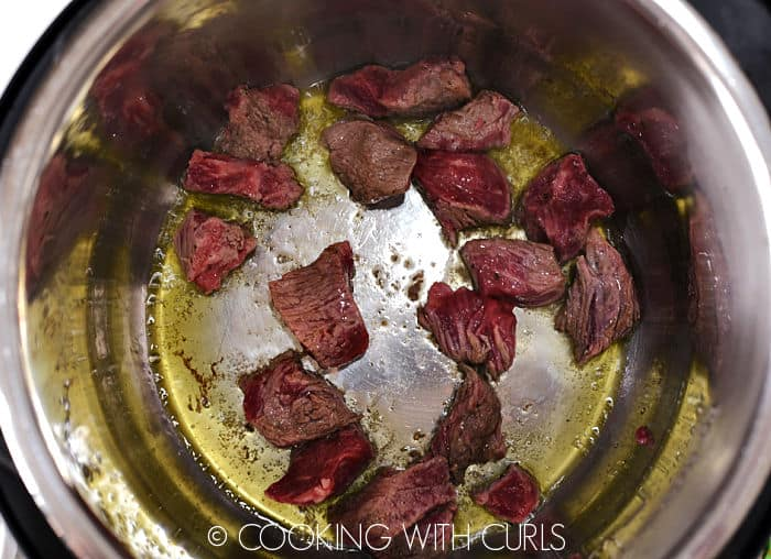 Oil and beef chunks sizzling in a pressure cooker.