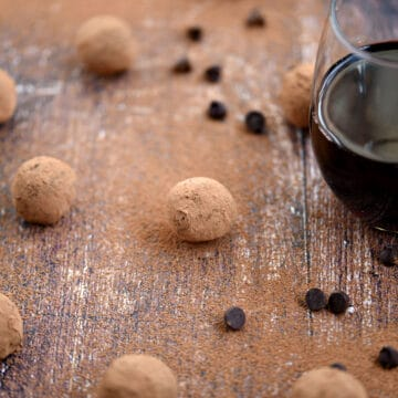 Cocoa covered red wine chocolate truffles on a wooden surface surrounded by cocoa powder, chocolate chips and a glass of wine.