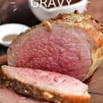 Medium-rare roast beef sliced on a dark wood cutting board with a bowl of gravy in the background and title graphic across the top.