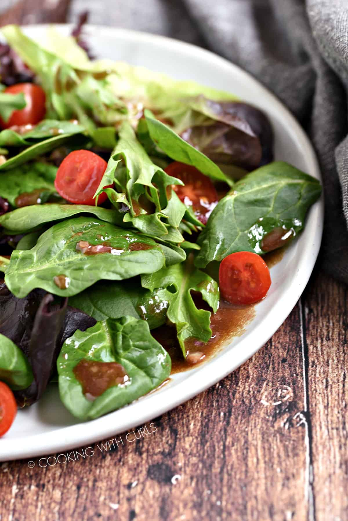 Side salad topped with Balsamic Vinaigrette and grape tomatoes.